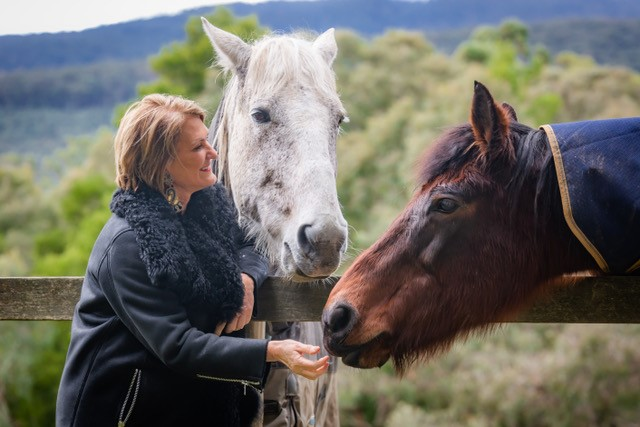 A woman with a white horse and a dark brown horse (James)